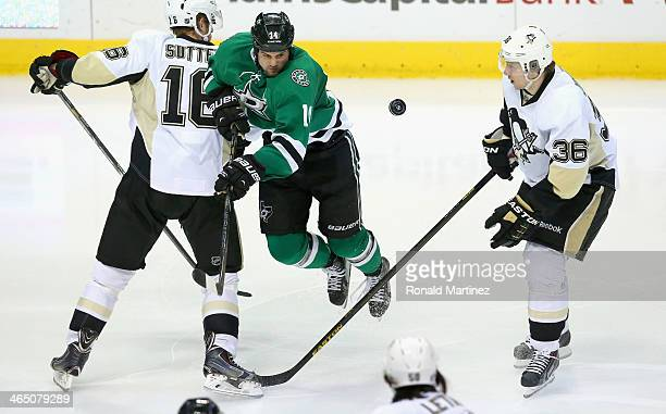 Jamie Benn of the Dallas Stars skates the puck against Brandon Sutter of the Pittsburgh Penguins and Jussi Jokinen of the Pittsburgh Penguins in the...