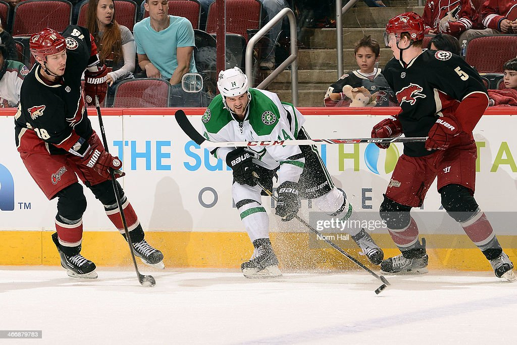 Jamie Benn #14 of the Dallas Stars skates with the puck between David Moss #18 and Connor Murphy #5 of the Phoenix Coyotes during the third period at Jobing.com Arena on February 4, 2014 in Glendale, Arizona.