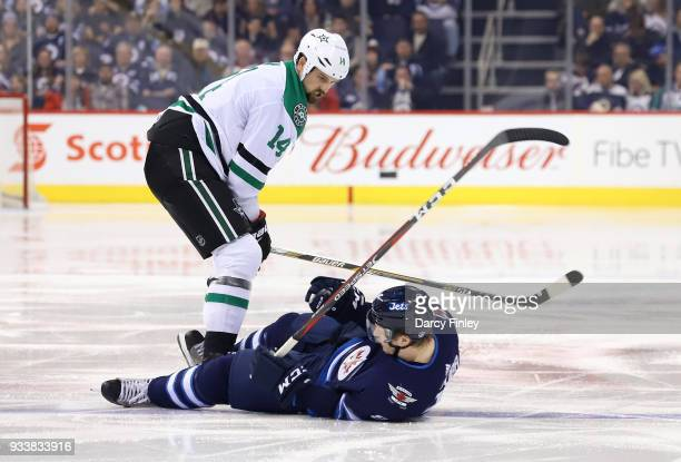 Jamie Benn of the Dallas Stars stares down at Jacob Trouba of the Winnipeg Jets after colliding with a check during third period action at the Bell...