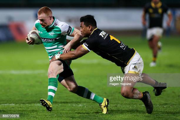 Jamie Booth of Manawatu evades the tackle of Julian Savea of Wellington during the round one Mitre 10 Cup match between Manawatu and Wellington at...