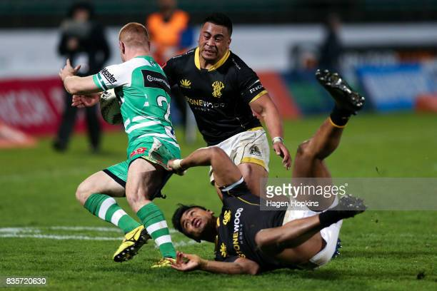 Jamie Booth of Manawatu is tackled by Asafo Aumua and Julian Savea of Wellington during the round one Mitre 10 Cup match between Manawatu and...