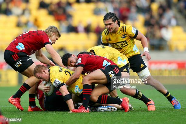 Jamie Booth of the Hurricanes is tackled by Richie Mo'unga of the Crusaders during the round 2 Super Rugby Aotearoa match between the Hurricanes and...