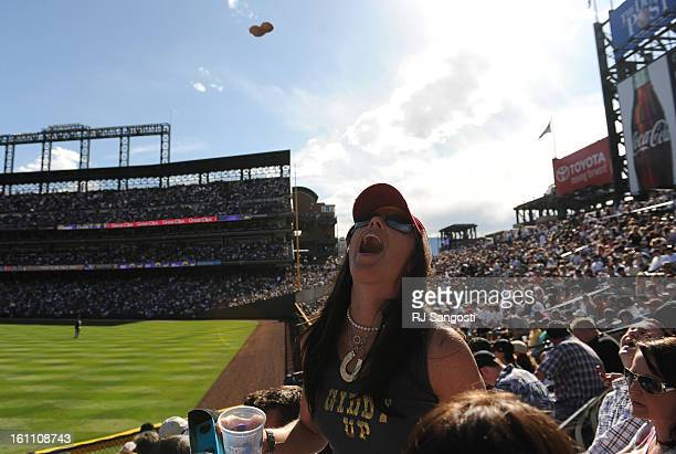 Jamie Bourbonnie from Denver tries to catch a thrown peanut during the 2010 Colorado Rockies home opener against the San Diego Padres at Coors Field...