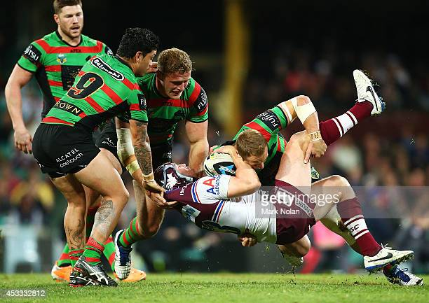 Jamie Buhrer of the Eagles is tackled during the round 22 AFL match between the South Sydney Rabbitohs and the Manly Sea Eagles at Sydney Cricket...