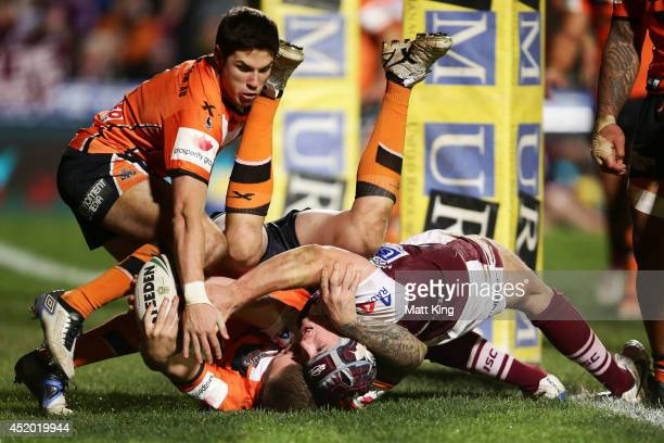 Jamie Buhrer of the Sea Eagles is held up over the line by Blake Austin of the Tigers during the round 18 NRL match between the Manly Warringah Sea...