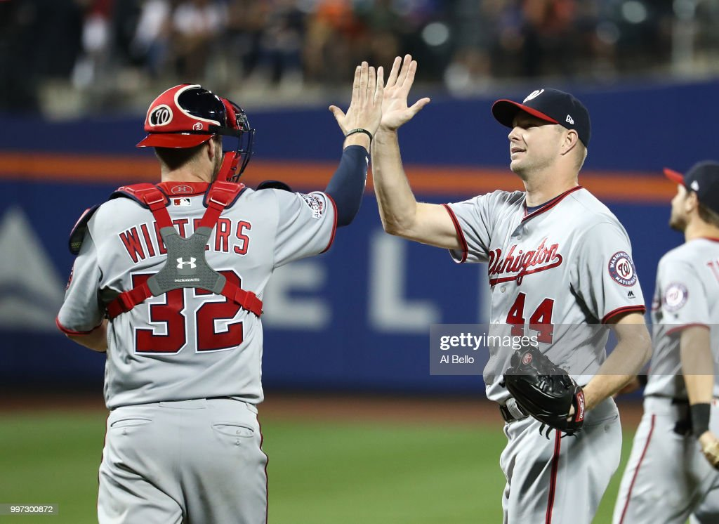 Jamie Burke and Ryan Madson #44 of the Washington Nationals celebrate a 5-4 win against the New York Mets during their game at Citi Field on July 12, 2018 in New York City.