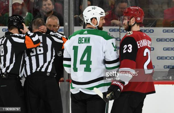 Jamie BVenn of the Dallas Stars and Oliver Ekman-Larsson of the Arizona Coyotes talk near the penalty box as officials review a play during the...