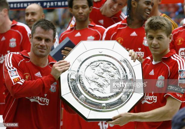 Jamie Carragher and Steven Gerrard of Liverpool hold the trophy following their team's victory during the FA Community Shield match between Liverpool...