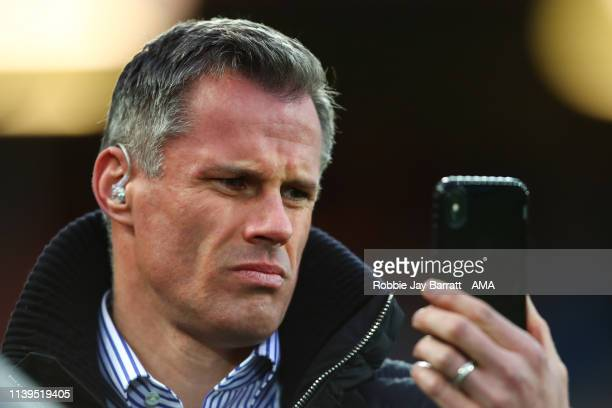 Jamie Carragher films on his iPhone during the Premier League match between Liverpool FC and Huddersfield Town at Anfield on April 26 2019 in...