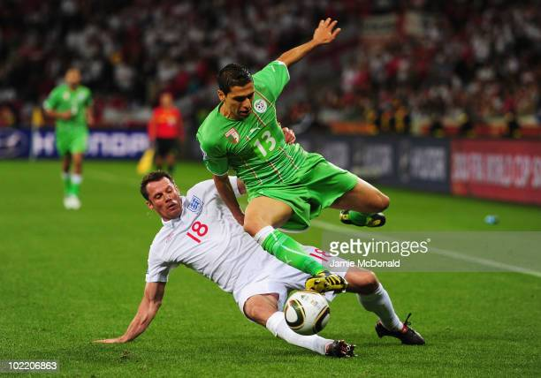 Jamie Carragher of England tackles Karim Matmour of Algeria during the 2010 FIFA World Cup South Africa Group C match between England and Algeria at...