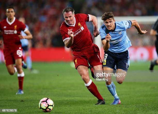 Jamie Carragher of Liverpool competes for the ball against George Blackwood of Sydney FC during the International Friendly match between Sydney FC...