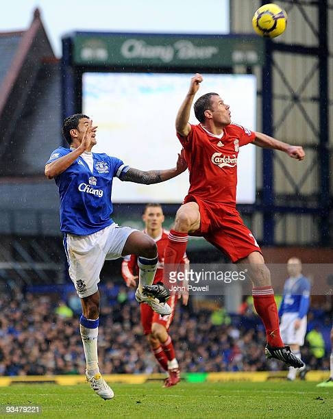 Jamie Carragher of Liverpool goes up with Tim Cahill of Everton during the Barclays Premier League match between Everton and Liverpool at Goodison...