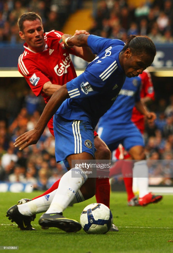 Jamie Carragher of Liverpool (L) tussles with Didier Drogba of Chelsea during the Barclays Premier League match between Chelsea and Liverpool at Stamford Bridge on October 4, 2009 in London, England.