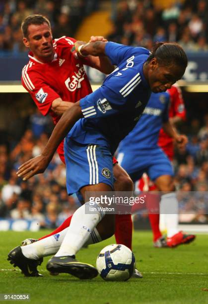 Jamie Carragher of Liverpool tussles with Didier Drogba of Chelsea during the Barclays Premier League match between Chelsea and Liverpool at Stamford...