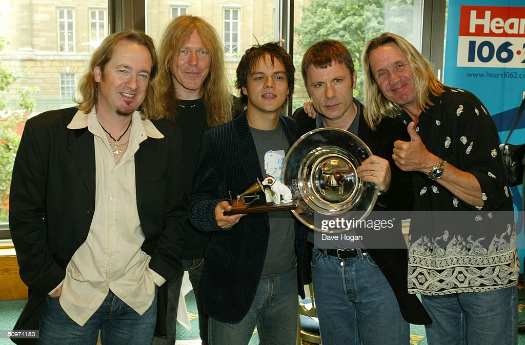 Jamie Cullum with his award for HMV Best New Music (C) poses with members of the heavy metal band Iron Maiden (L to R Adrian Smith, Janick Gers, Cullum, Bruce Dickinson, Nicko McBrain) with the award for Deluxe Space Special Achievement Award pose with in the pressroom at the Nordoff-Robbins O2 Silver Clef Awards at the Inter-Continental Hotel on June 18, 2004 in London.