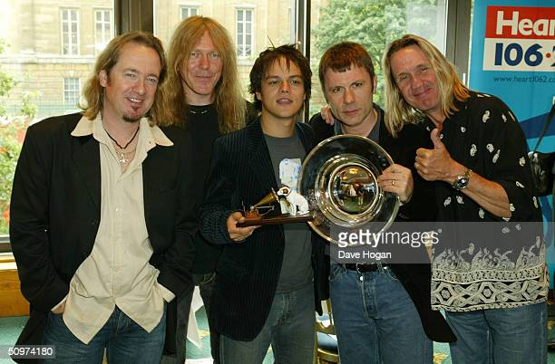 Jamie Cullum with his award for HMV Best New Music poses with members of the heavy metal band Iron Maiden with the award for Deluxe Space Special...