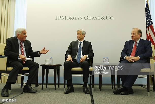 Jamie Dimon chairman and CEO of JPMorgan Chase Co is flanked by Detroit Mayor Mike Duggan and Walter Isaacson president of the Aspen Institute during...