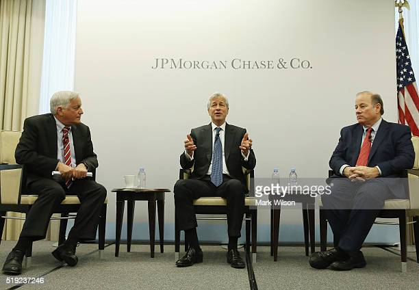 Jamie Dimon chairman and CEO of JPMorgan Chase Co speaks while flanked by Detroit Mayor Mike Duggan and by Walter Isaacson president of the Aspen...