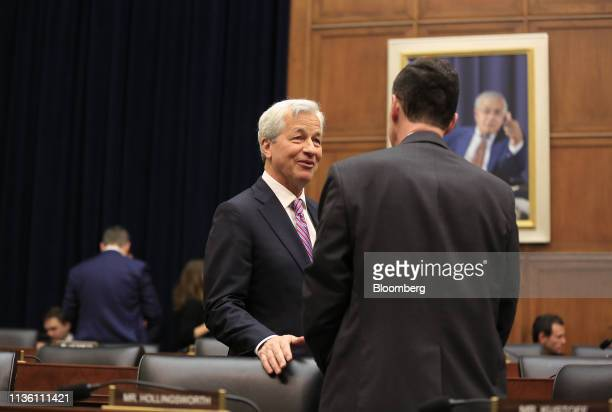 Jamie Dimon, chief executive officer of JPMorgan Chase & Co., left, speaks with a lawmaker before the start of a House Financial Services Committee...