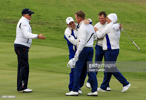 Jamie Donaldson and Lee Westwood of Europe are congratulated by Europe team captain Paul McGinley and vice captain Sam Torrance after their victory...