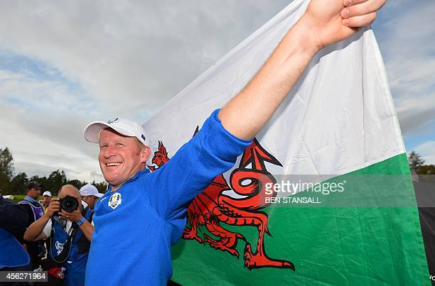 Jamie Donaldson of Wales holds the Welsh flag after Team Europe retained the Ryder Cup on the final day of the Ryder Cup golf tournament at the...
