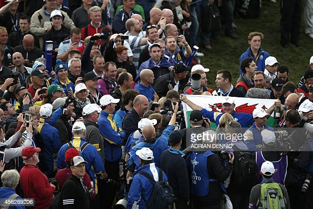 Jamie Donaldson of Wales holds the Welsh flag on the 15th green after he retained the Ryder Cup for Team Europe during Sunday's Singles matches on...