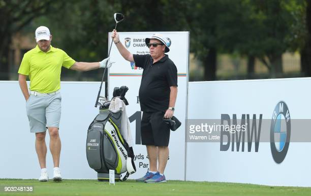 Jamie Donaldson of Wales is given a club by caddie Michael 'Mick' Donaghy as he plays a practice round ahead of the BMW South African Open...