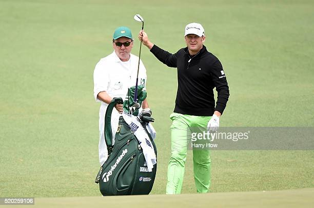 Jamie Donaldson of Wales pulls a club from his bag as caddie Michael Mick Donaghy looks on during the final round of the 2016 Masters Tournament at...