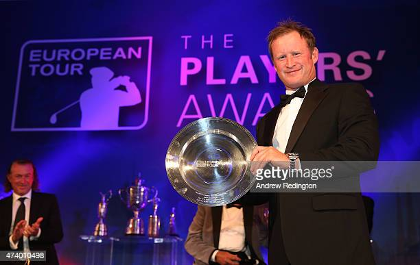 Jamie Donaldson of Wales receives the Shot of the Year award from Paul McGinley of Ireland during the European Tour Players' Awards ahead of the BMW...