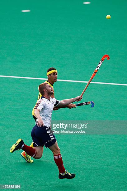 Jamie Dwyer of Australia battles for the ball with Ashley Jackson of Great Britain during the Fintro Hockey World League Semi-Final match between...