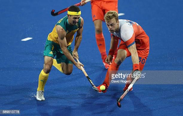 Jamie Dwyer of Australia is challenged by Mink van der Weerden during the Men's hockey quarter final match between the Netherlands and Australia on...