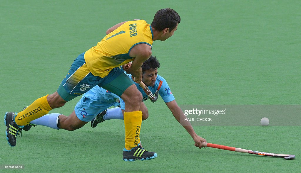 Jamie Dwyer of Australia (L) makes a pass past Manpreet Singh of India (R) during the second semifinal at the men's Hockey Champions Trophy tournament in Melbourne on December 8, 2012. IMAGE STRICTLY RESTRICTED TO EDITORIAL USE - STRICTLY NO COMMERCIAL USE AFP PHOTO / Paul CROCK