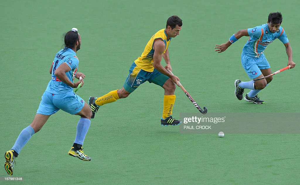 Jamie Dwyer of Australia (C) runs between Manpreet Singh (L) and Sadar Singh of India (R) during the second semifinal at the men's Hockey Champions Trophy tournament in Melbourne on December 8, 2012. IMAGE STRICTLY RESTRICTED TO EDITORIAL USE - STRICTLY NO COMMERCIAL USE AFP PHOTO / Paul CROCK