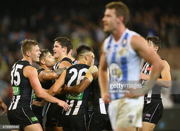 Jamie Elliott of the Magpies is congratulated by team mates after kicking a goal whilst Lachlan Hansen of the Kangaroos looks dejected during the...
