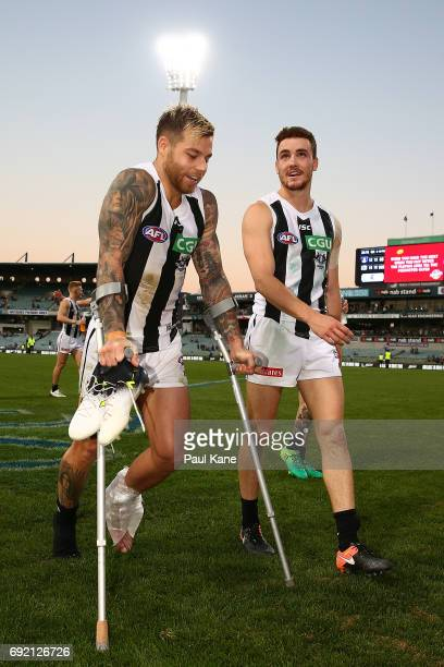 Jamie Elliott of the Magpies leaves the field of play on crutches after winning the round 11 AFL match between the Fremantle Dockers and the...