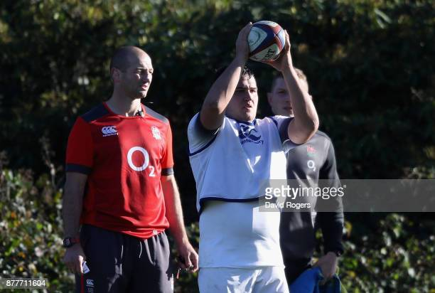 Jamie George prepares to throw the ball as forwards coach Steve Borthwick looks on during the England training session held at Pennyhill Park on...