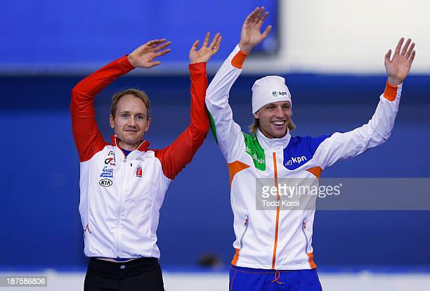 Jamie Gregg of Canada and Ronald Mulder of the Netherlands wave to the crowd before getting their bronze medals in the men's 500 meter race during...