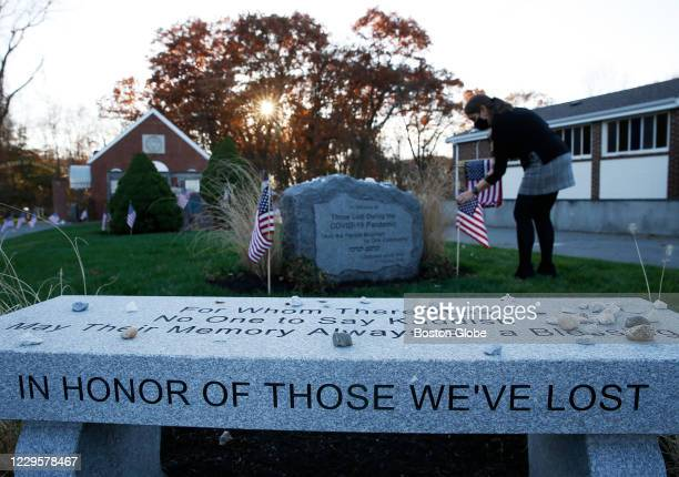 Jamie H. Cotel Executive Director, Jewish Cemetery Association of Massachusetts, plants flags around a plot of land with two memorials inside Baker...