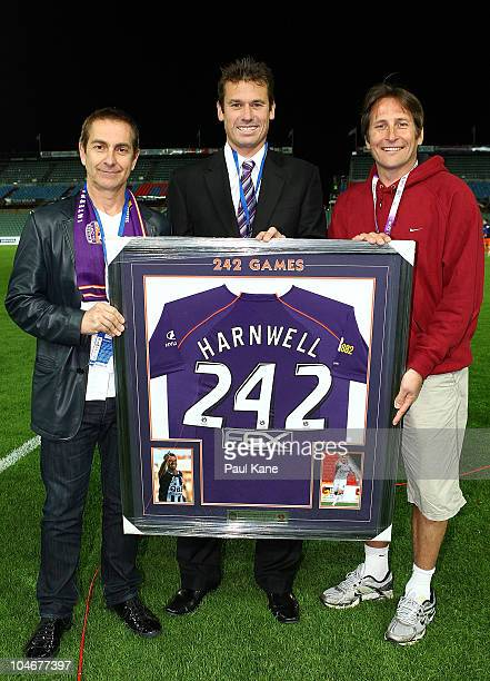 Jamie Harnwell of the Glory is presented with a framed playing top and commemorative coin by team owner Tony Sage and former club champion Bobby...