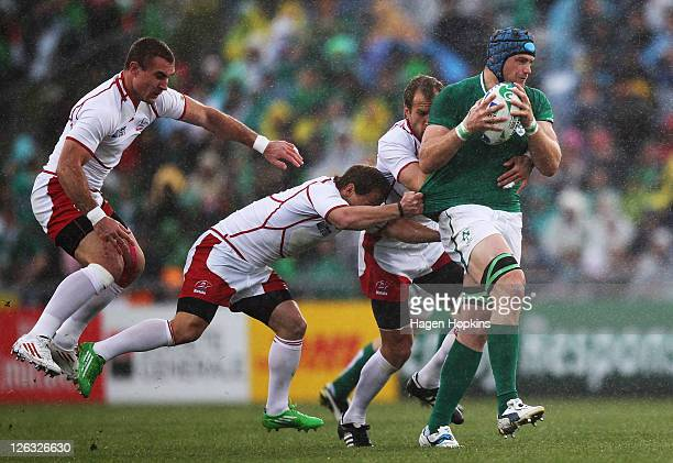 Jamie Heaslip of Ireland is tackled by Andrey Kuzin Alexander Yanyushkin and Vladimir Ostroushko during the IRB 2011 Rugby World Cup Pool C match...