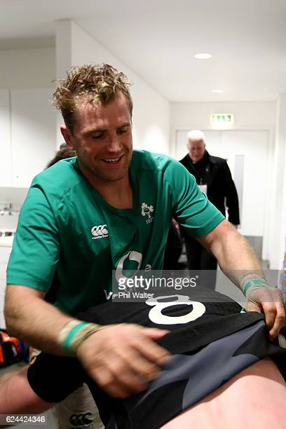Jamie Heaslip of Ireland removes the jersey from Kieran Read of New Zealand in the dressing room following the international rugby match between...