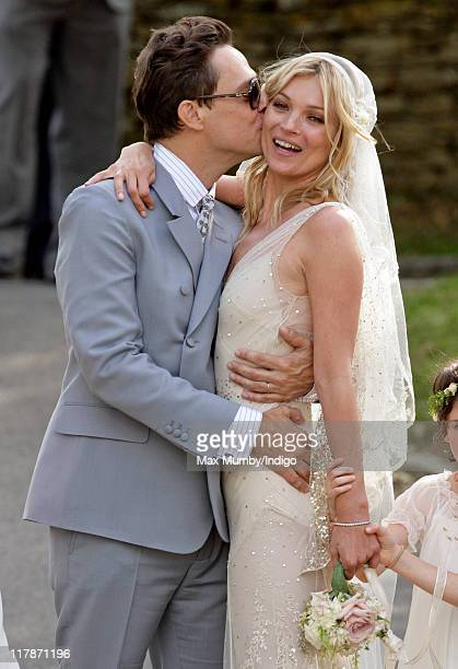 Jamie Hince and Kate Moss kiss as they leave St Peter's Church after their wedding on July 1 2011 in Southrop England