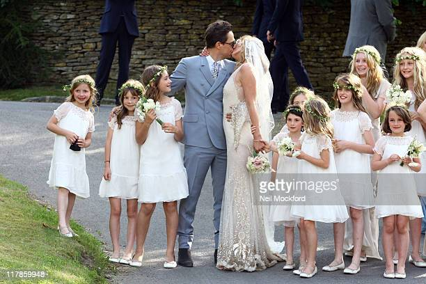 Jamie Hince kisses his new bride Kate Moss as their bridesmaids look on outside the church after their wedding on July 1 2011 in Southrop England