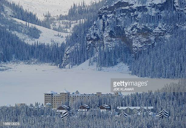 Jamie hotel worker of Fairmont Chateau Hotel shovels a snow between the hotel and a gateway to the Lake Louise early morning in Lake Louise Alberta...