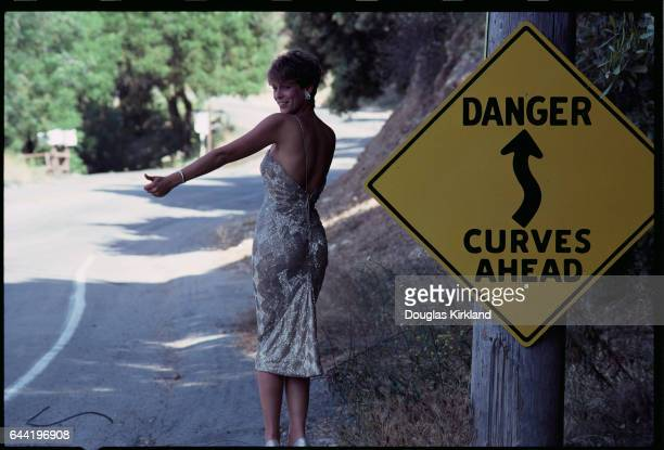 Jamie Lee Curtis Hitchhiking in Cocktail Dress