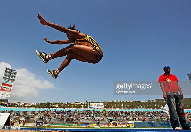 Jamie Lee Gordon of Manchester High flies past a judge in the girls 1319 long jump at National Stadium Kingston Jamaica Students from more than 100...