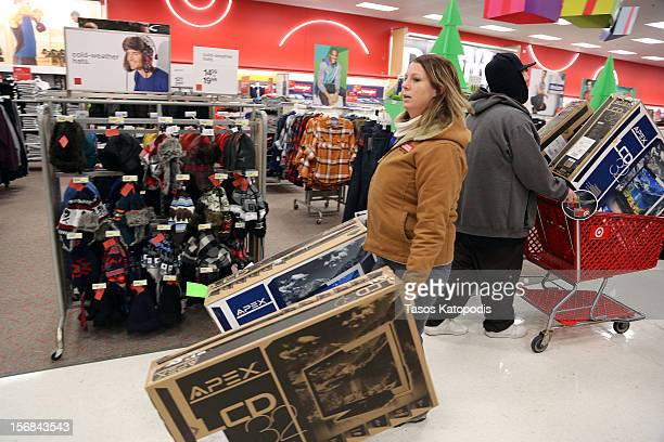 Jamie Loew of Griffith Indiana holds two flat screen tvs at a Kmart on Thanksgiving night November 22 2012 in Griffith Indiana City Many stores got a...