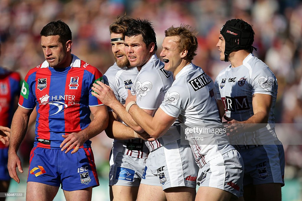 Jamie Lyon (C) of the Sea Eagles celebrates with team mates after scoring a try as Danny Buderus (L) looks on of the Knights during the round 24 NRL match between the Manly Warringah Sea Eagles and the Newcastle Knights at Brookvale Oval on August 19, 2012 in Sydney, Australia.
