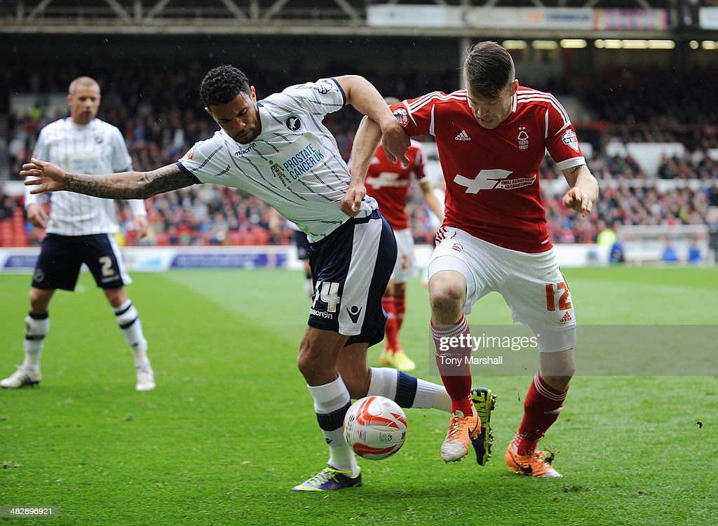 Jamie Mackie (R) of Nottingham Forest tackled by Carlos Edwards of Millwall during the Sky Bet Championship match between Nottingham Forest and Millwall at City Ground on April 05, 2014 in Nottingham, England,