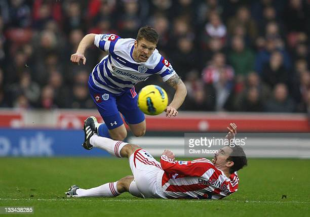 Jamie Mackie of Queens Park Rangers is tackled by Danny Higginbotham of Stoke City during the Barclays Premier League match between Stoke City and...